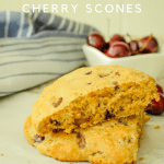 2 scones stacked on parchment paper with blue towel and cherries in back