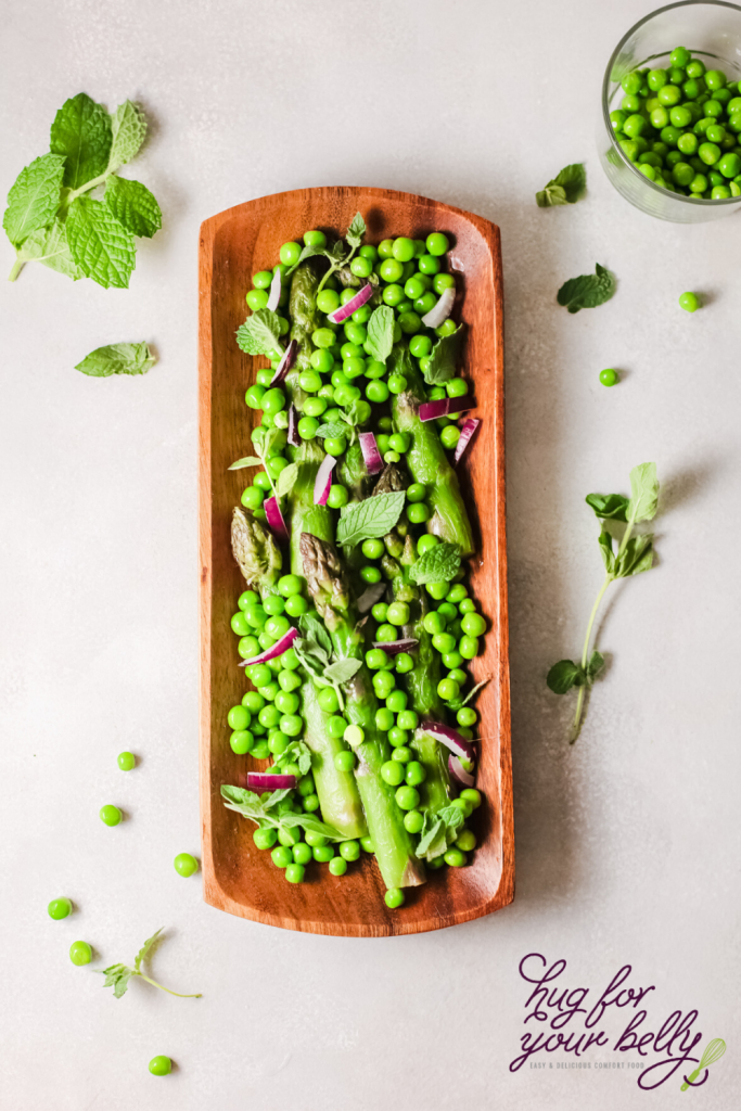 This asparagus and peas green salad is a delicious, delicate salad that's perfect for this season. Made with asparagus, peas, mint and pickled red onions and drizzled with a honey vinaigrette this salad is the star of any table. #salad #springflavor #asparagus #peas