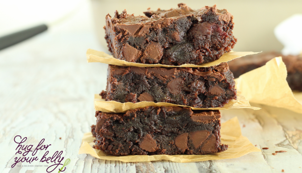 3 chocolate cherry brownies stacked with parchment paper in between