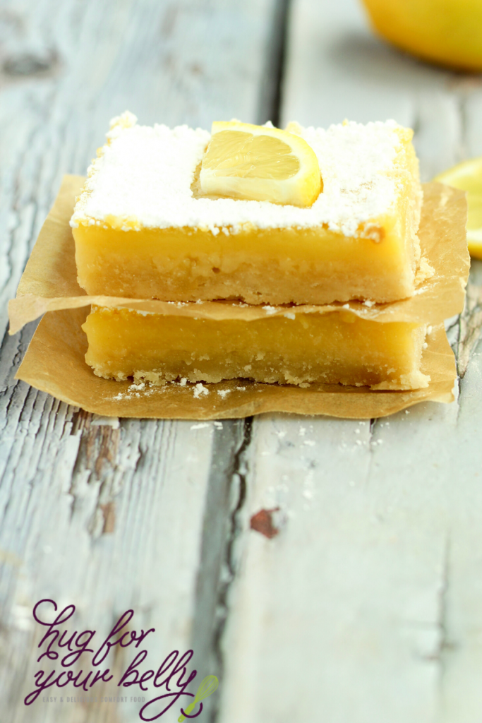 2 lemon bars stacked on brown parchment paper
