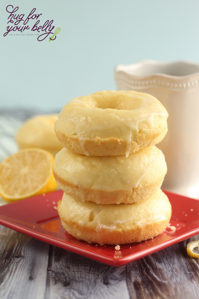 3 lemon donuts stacked on red plated, with white coffee cup behind them
