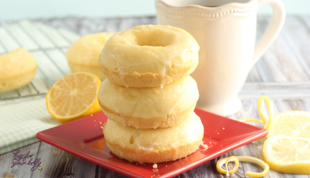 lemon donuts stacked on red plate, with white coffee cup behind them