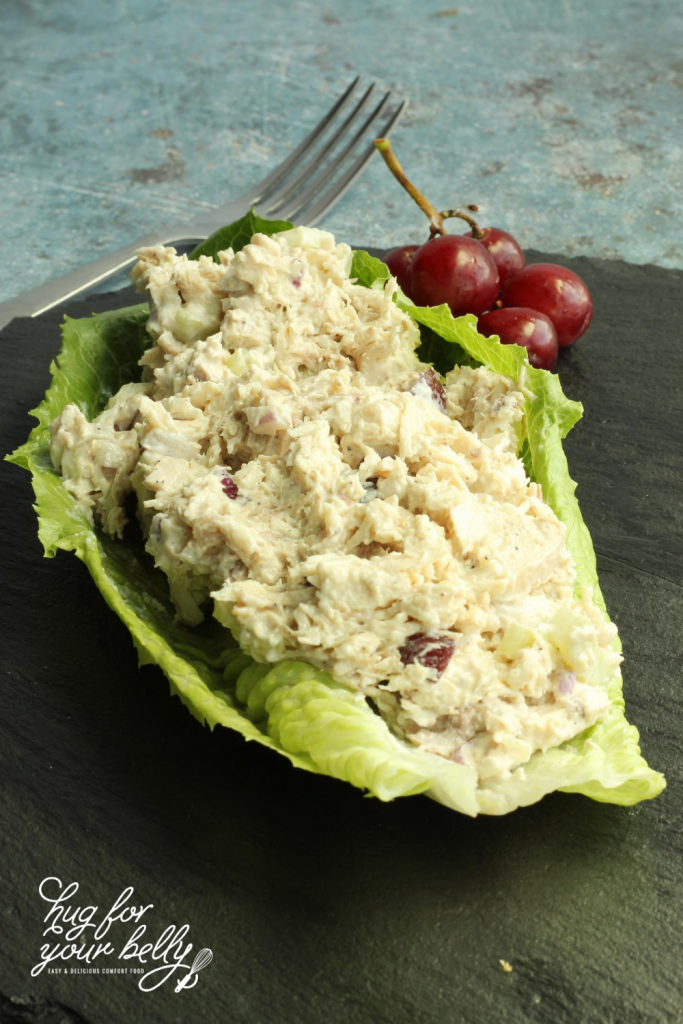chicken salad on bed of lettuce with grapes and fork