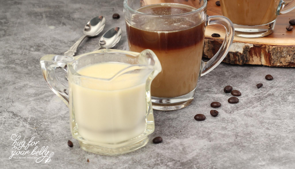 coffee creamer next to cup of coffee