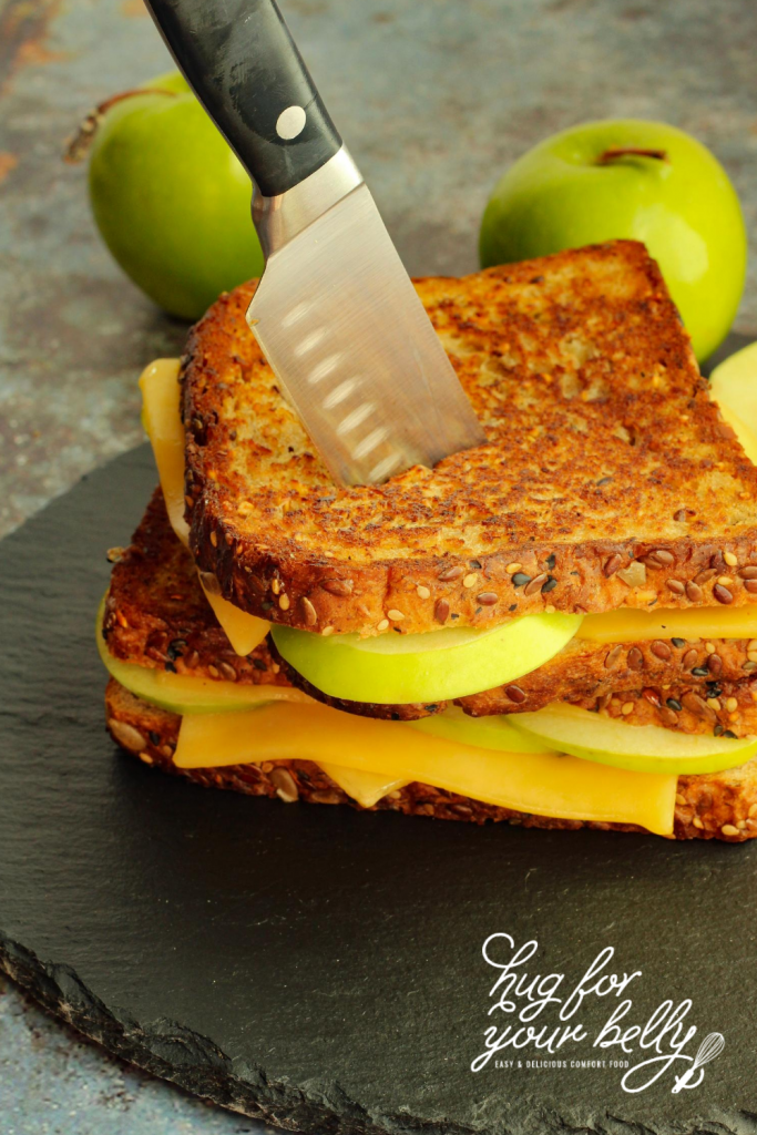 grilled cheese sandwiches stacked with knife through them