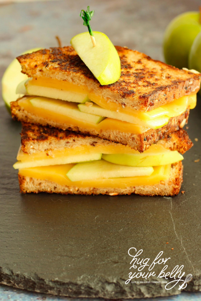 apple grilled cheese sliced in half and stacked on black platter