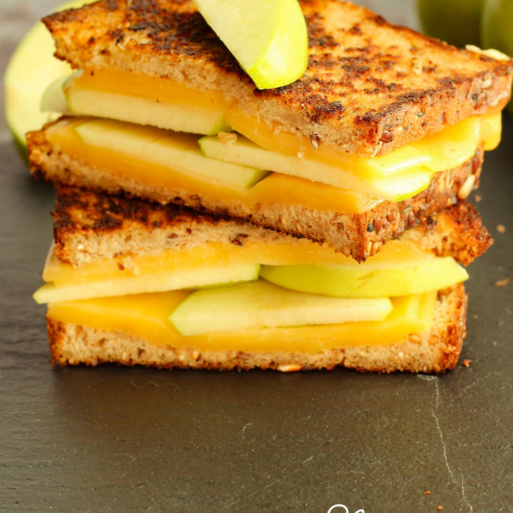 apple grilled cheese cut in half and stacked on black platter
