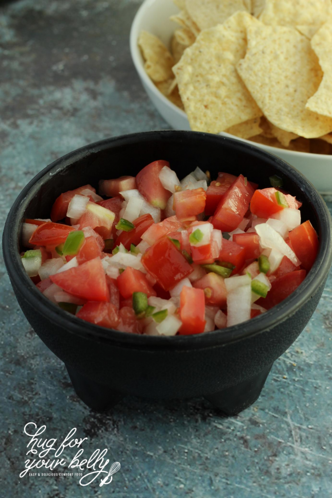 pico de gallo in black bowl with tortilla chips in back