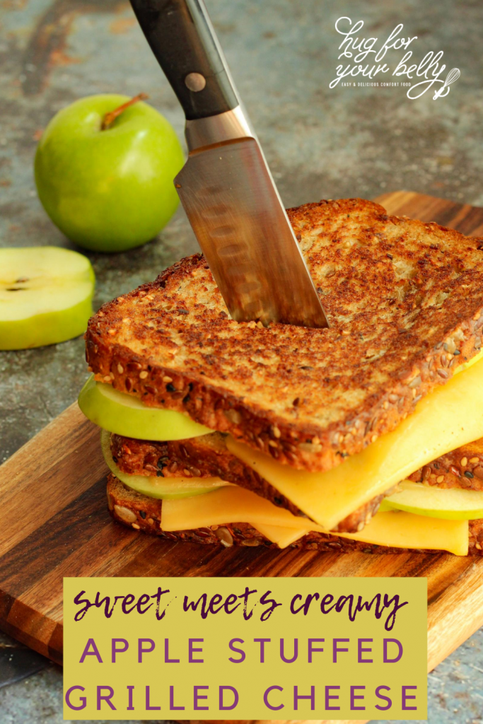 apple grilled cheese with knife through it on cutting board