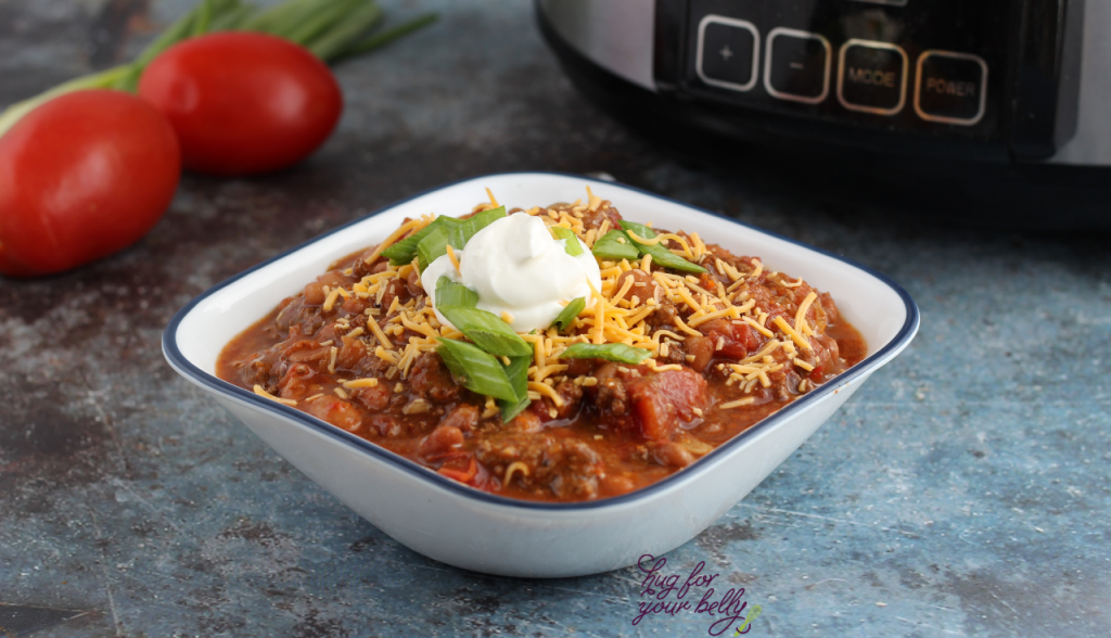chili in white bowl with cheese, onions, and sour cream on top