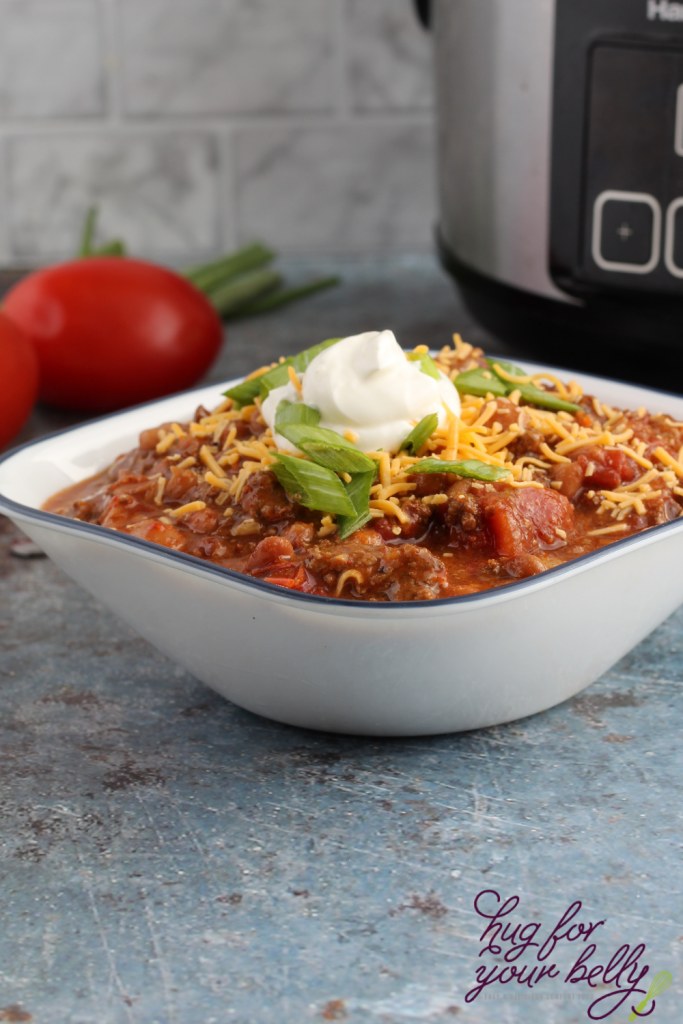 chili in bowl with sour cream, cheese, and chives