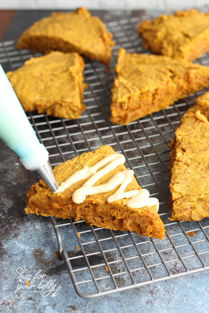 drizzling maple cream frosting on pumpkin scones