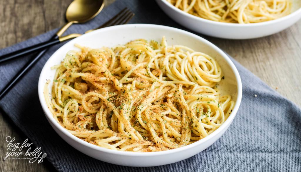 spaghetti aglio e olio in white bowl on gray cloth