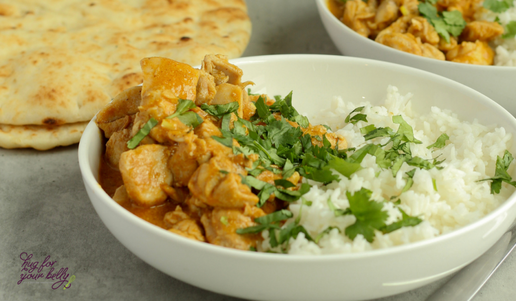 butter chicken over rice in white bowl