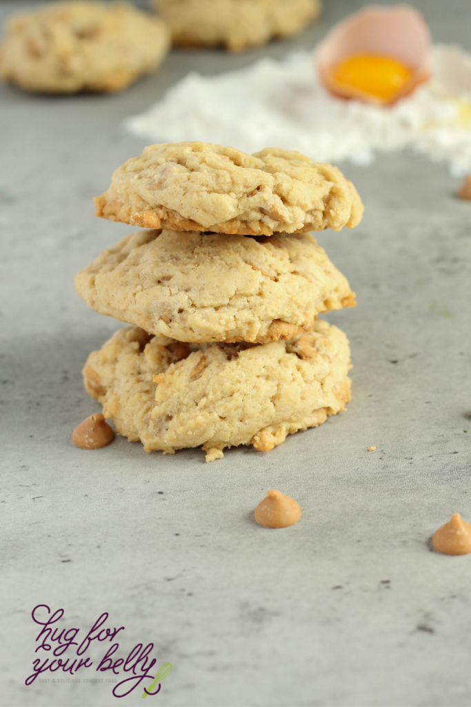 3 peanut butter chip cookies stacked on marble background