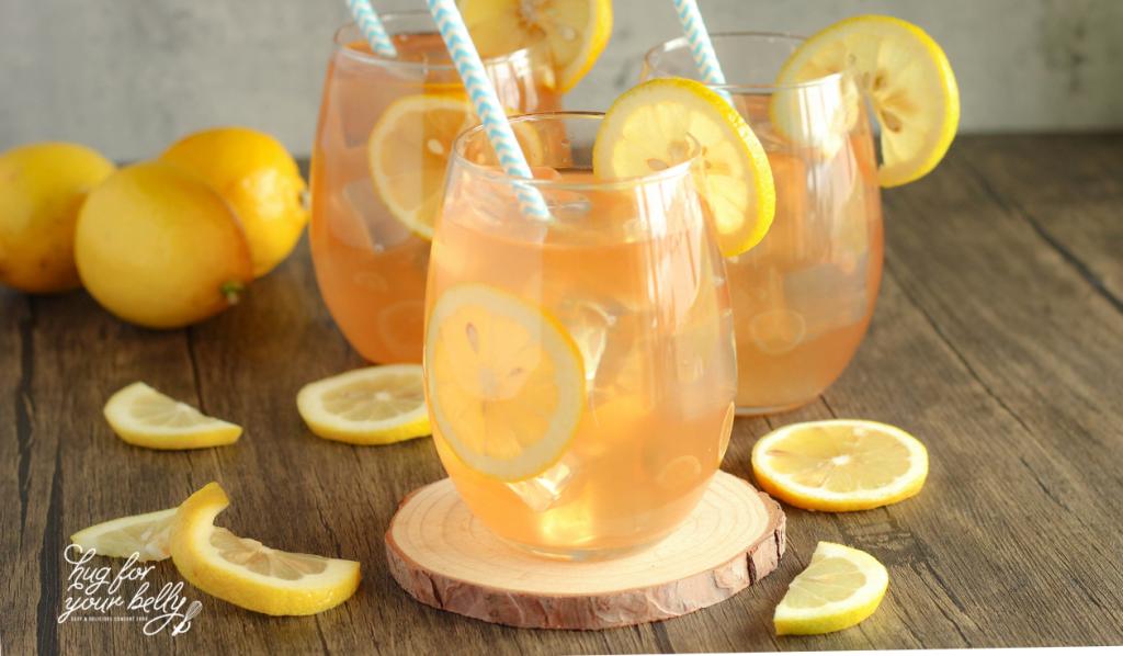 pink lemonade in glasses with lemon slices surrounding the glasses