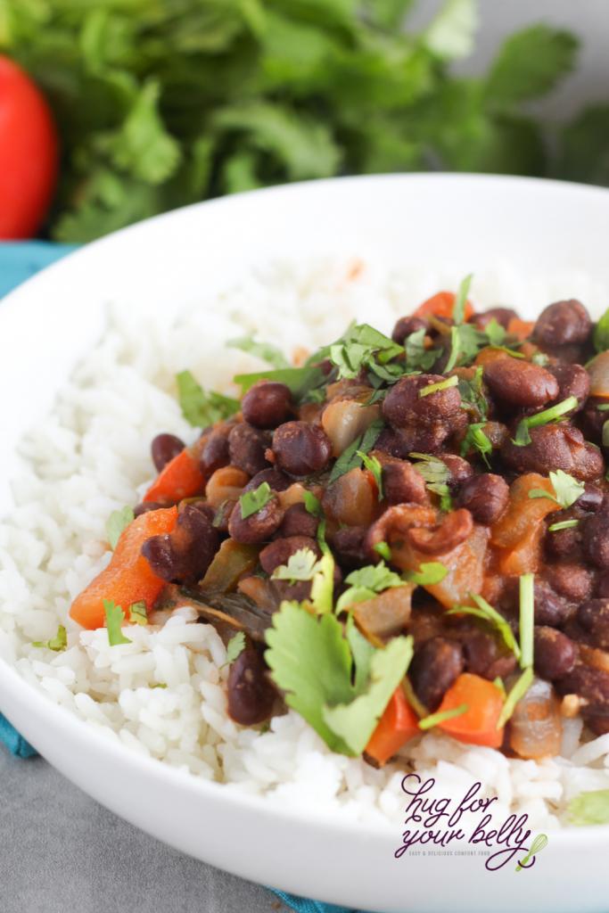 black beans over white rice in white bowl