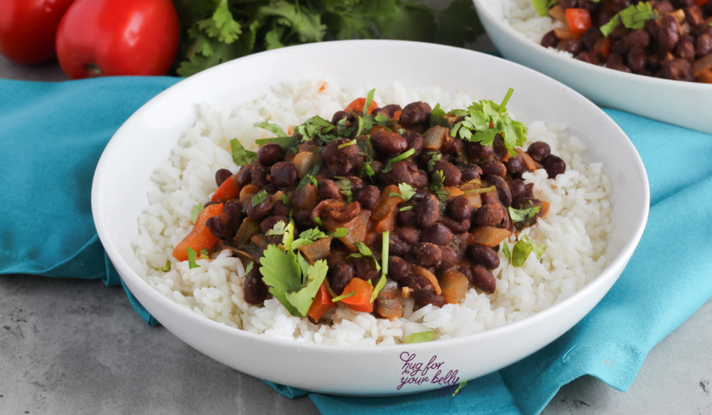 cuban black beans over white rice in a white bowl