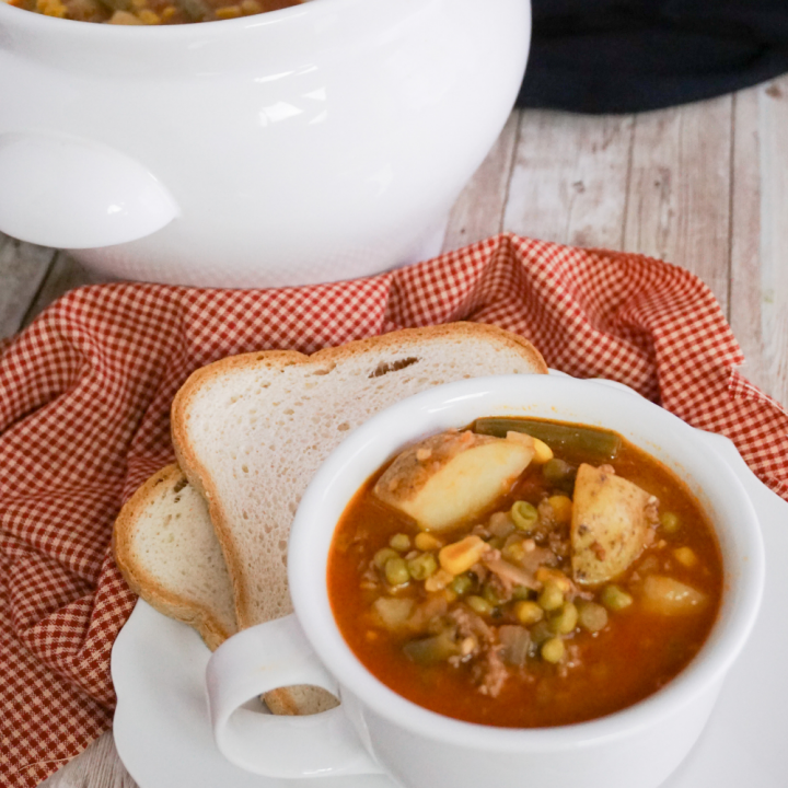 hamburger soup in white cup with a saucer and slice of bread
