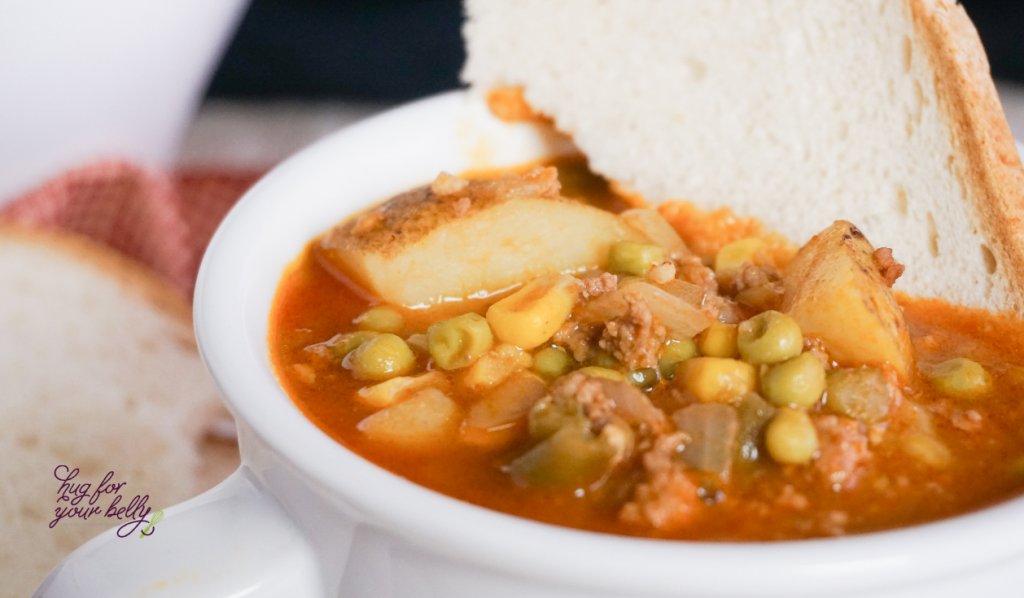 vegetables in a soup next to a slice of white bread